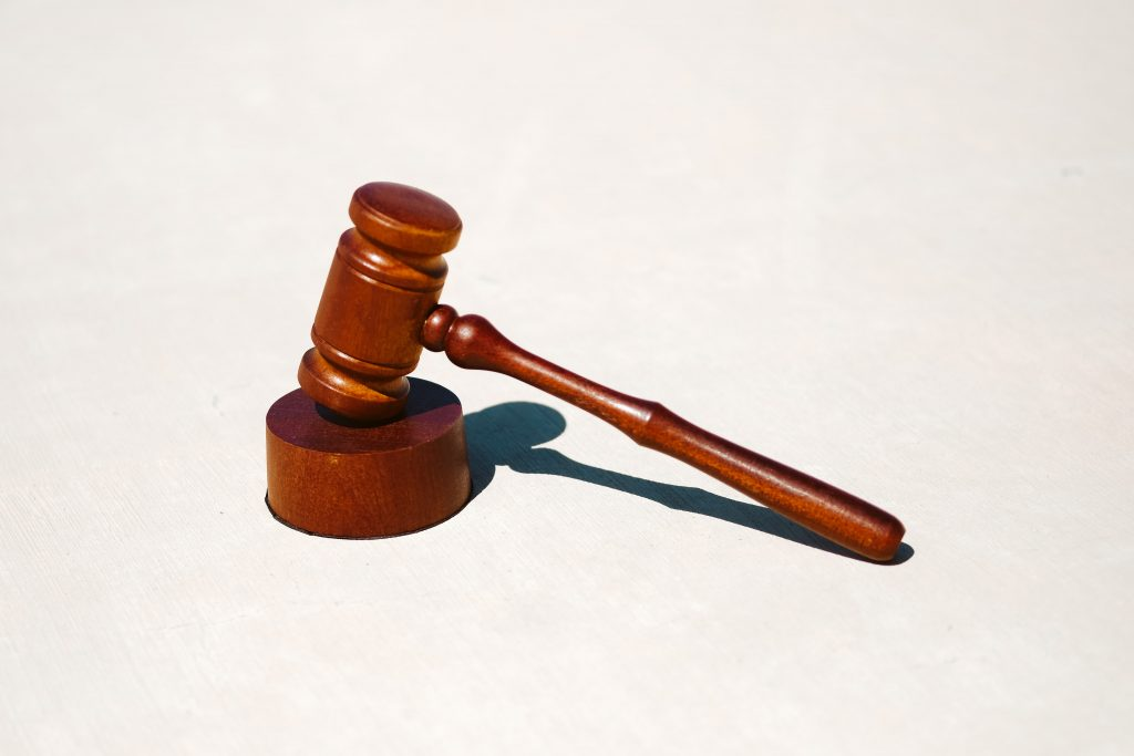 A wooden gavel on a white surface